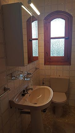 Badrummet med mycket förvaring i badrumsskåp och på hyllor, många krokar!